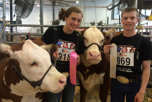 "Ashby and Jared Dauer with their Hereford Heifers ""Miss Neon"" and ""Katie"" at the Junior National Hereford Expo."
